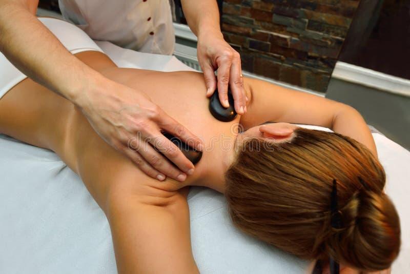 Jonge vrouw die terwijl de massagetherapeut mas is liggen stock foto's