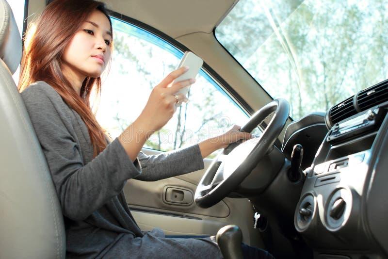 Jonge vrouw die terwijl het drijven texting royalty-vrije stock fotografie
