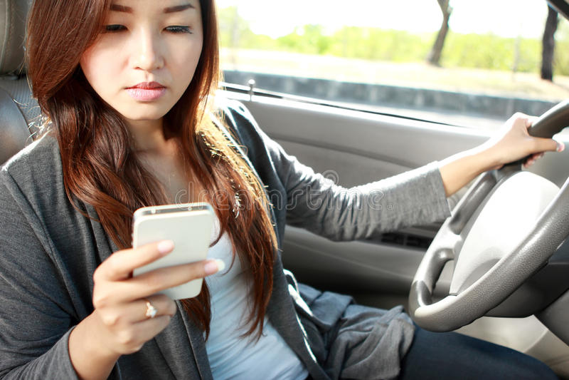 Jonge vrouw die terwijl het drijven van een auto texting royalty-vrije stock afbeeldingen