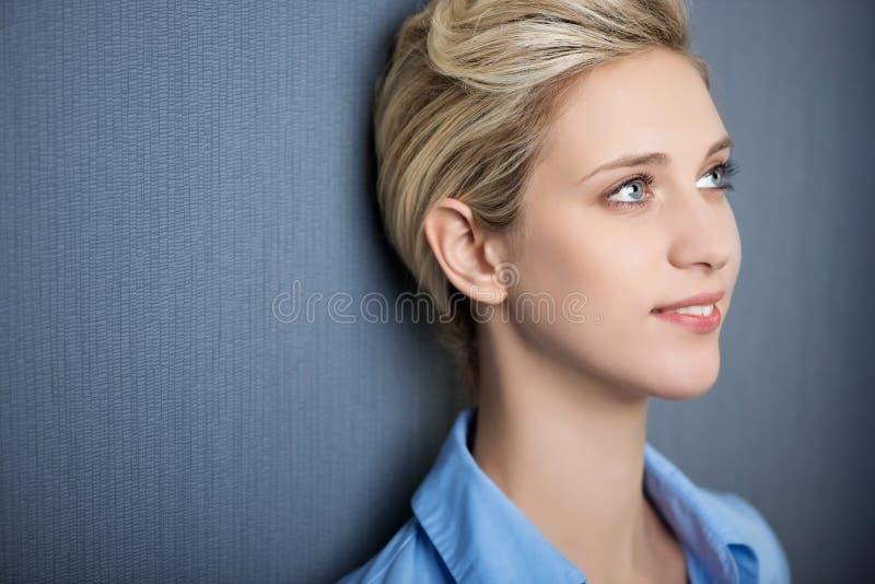 Jonge Vrouw die terwijl het Kijken weg tegen Blauwe Muur glimlachen royalty-vrije stock afbeelding