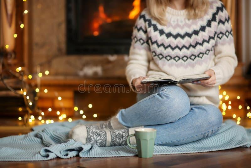 Jonge vrouw die terwijl het lezen van boek in woonkamer ontspannen stock foto