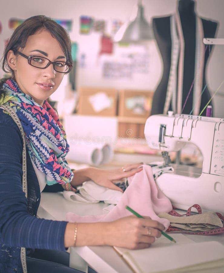 Jonge vrouw die terwijl het zitten op haar werkende plaats naaien royalty-vrije stock fotografie