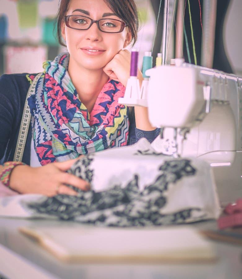 Jonge vrouw die terwijl het zitten op haar werkende plaats naaien royalty-vrije stock afbeelding