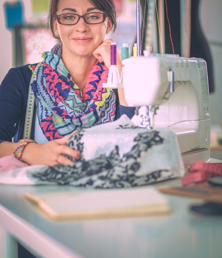 Jonge vrouw die terwijl het zitten op haar werkende plaats naaien stock afbeelding