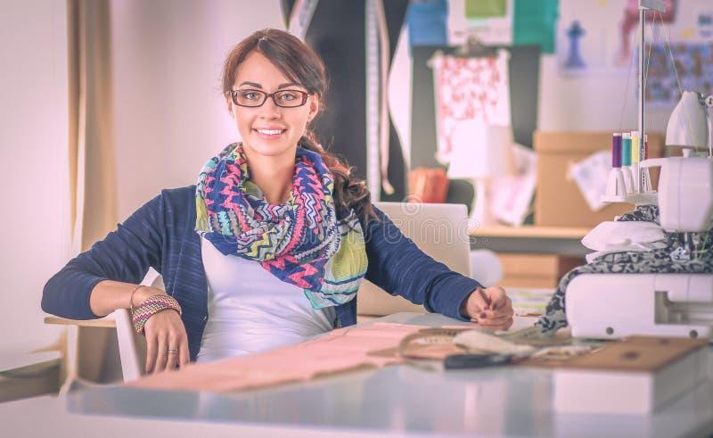 Jonge vrouw die terwijl het zitten op haar werkende plaats naaien stock foto