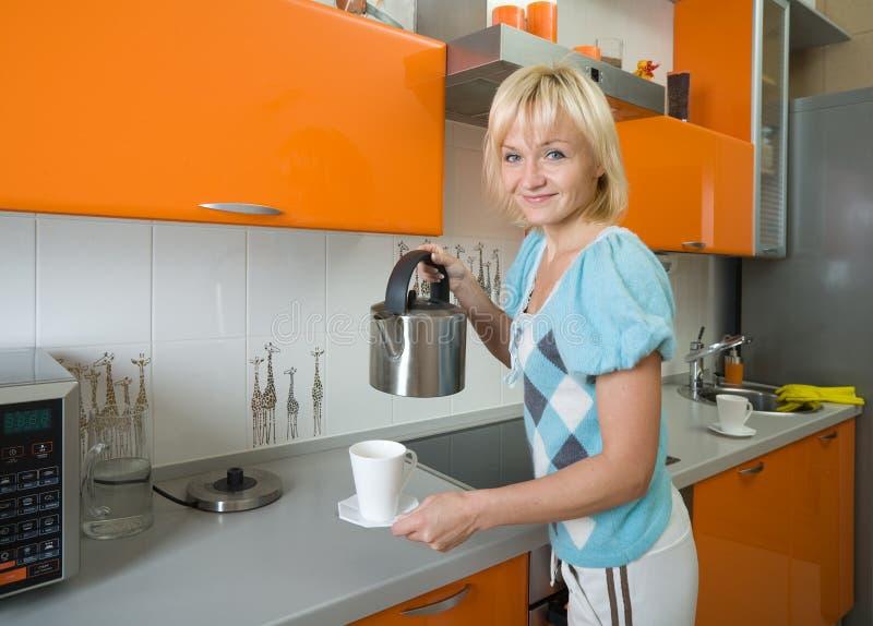 Jonge vrouw die thee voorbereidt stock afbeelding