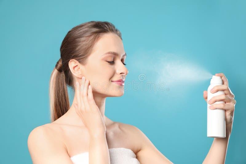 Jonge vrouw die thermisch water op gezicht toepassen tegen kleurenachtergrond stock fotografie