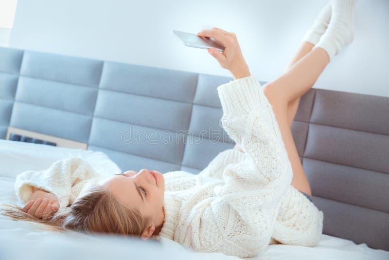 Jonge vrouw die thuis benen omhoog op muur in bed leggen die sweater selfie foto's dragen stock afbeeldingen