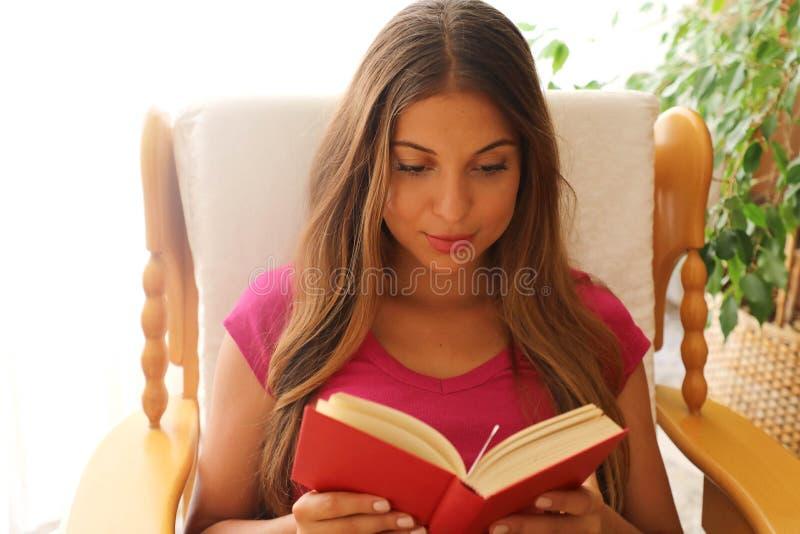 Jonge vrouw die thuis bij het comfortabele stoel ontspannen in haar boek van de woonkamerlezing zitten royalty-vrije stock fotografie