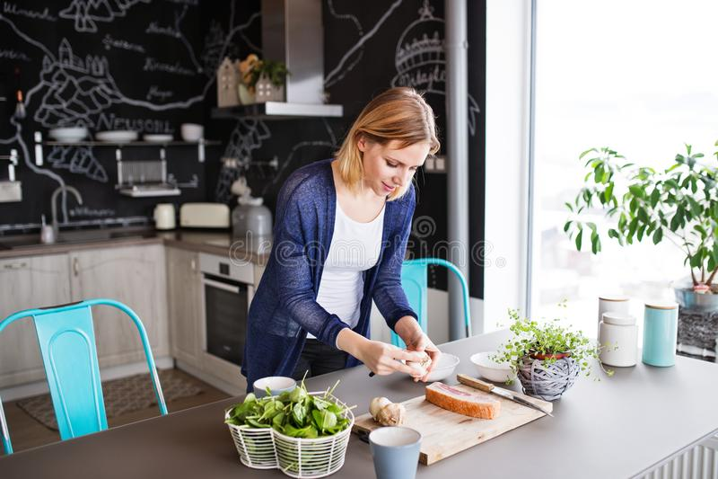Jonge vrouw die thuis kookt stock afbeeldingen