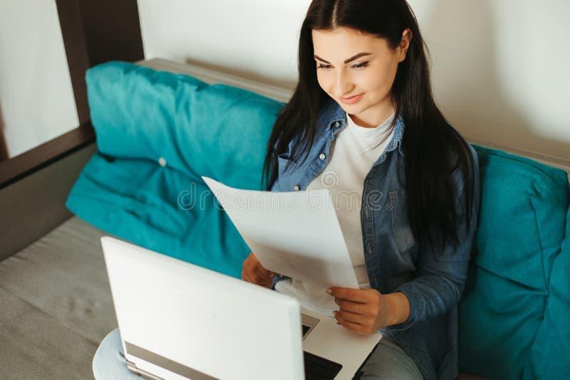 Jonge vrouw die thuis online werkt met een laptop royalty-vrije stock afbeelding