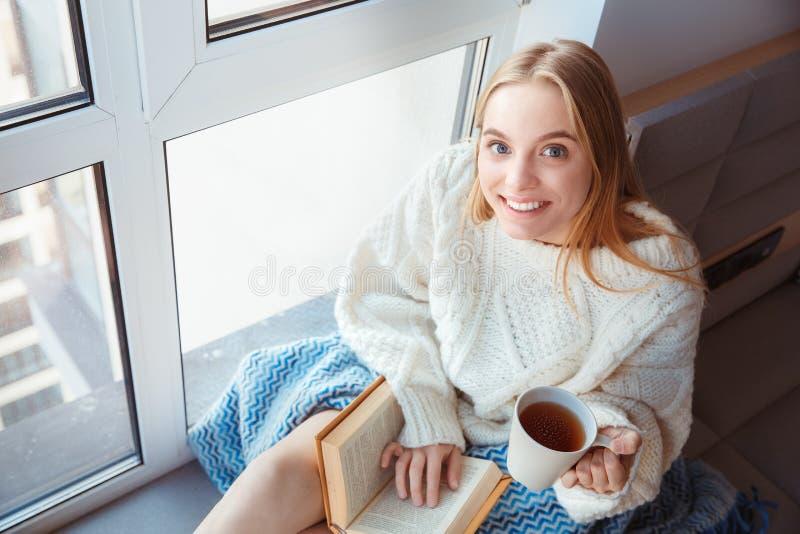 Jonge vrouw die thuis op de winterconcept van de venstervensterbank het drinken het boek van de theelezing zitten stock foto's