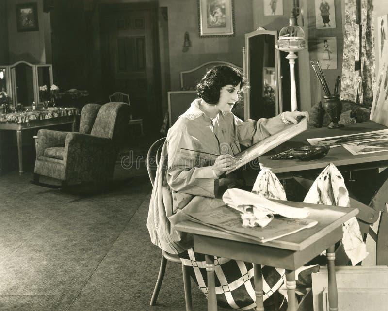 Jonge vrouw die thuis schildert stock foto's