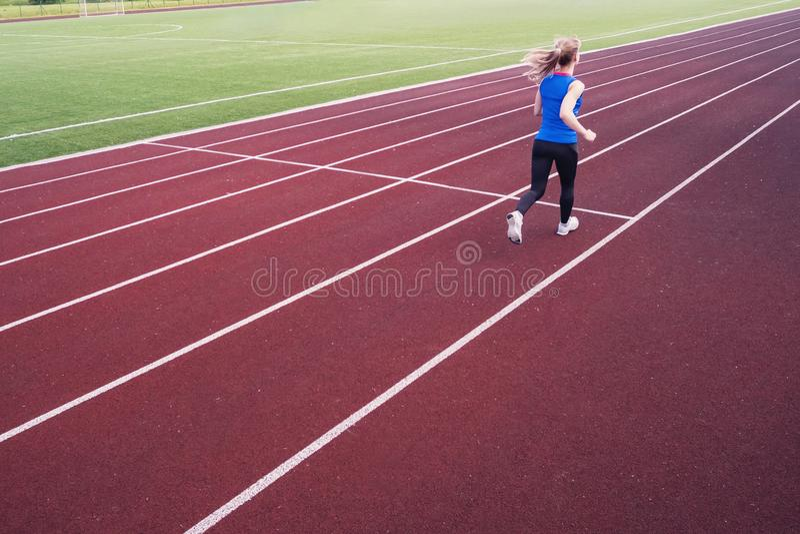 Jonge vrouw die tijdens zonnige avond op stadionspoor lopen Een blonde in een blauwe t-shirt en zwarte beenkappenlooppas over royalty-vrije stock foto's