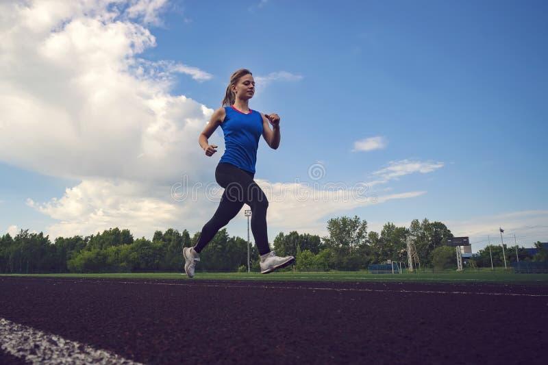 Jonge vrouw die tijdens zonnige avond op stadionspoor lopen Een blonde in een blauwe t-shirt en zwarte beenkappenlooppas over het stock foto