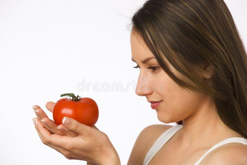 Jonge vrouw die tomaat in haar handen bekijkt royalty-vrije stock afbeeldingen
