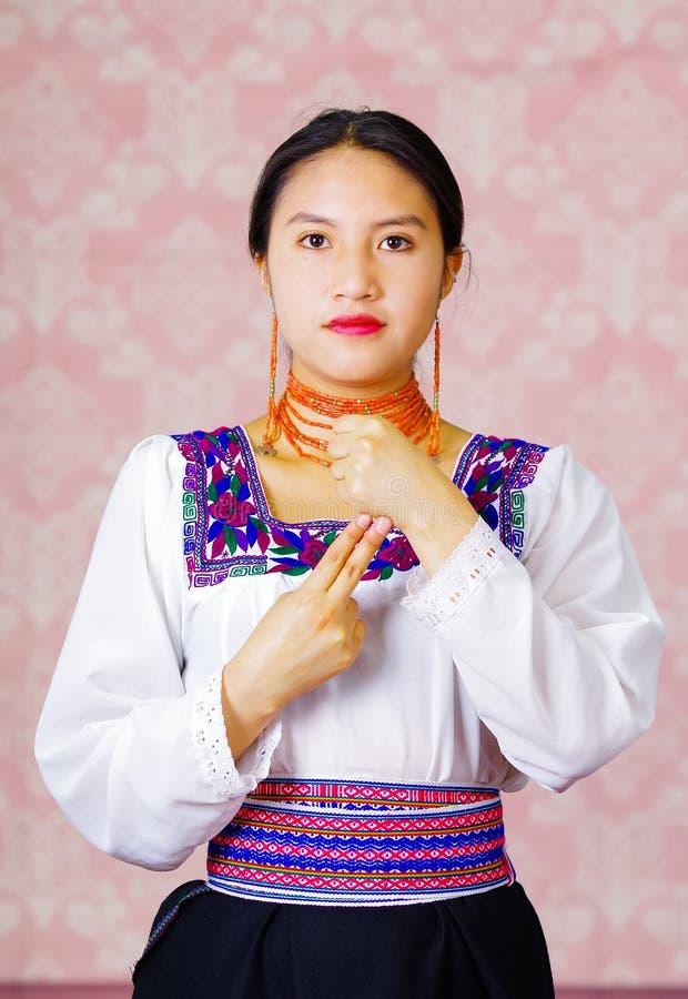 Jonge vrouw die traditionele Andeskleding draagt, die camera onder ogen ziet die gebarentaalwoord voor allebei doet stock foto's