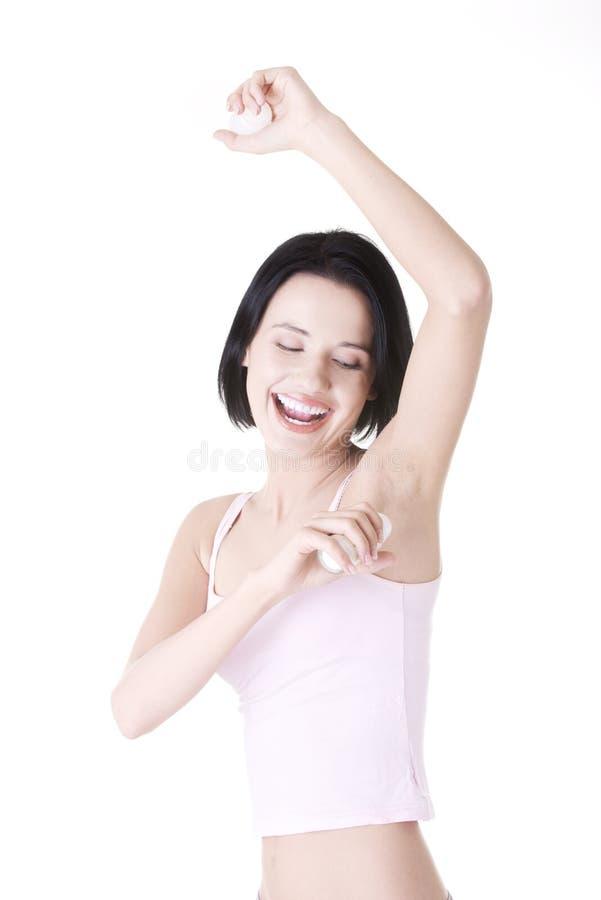 Jonge vrouw die transpiratiewerend middel gebruikt stock afbeeldingen