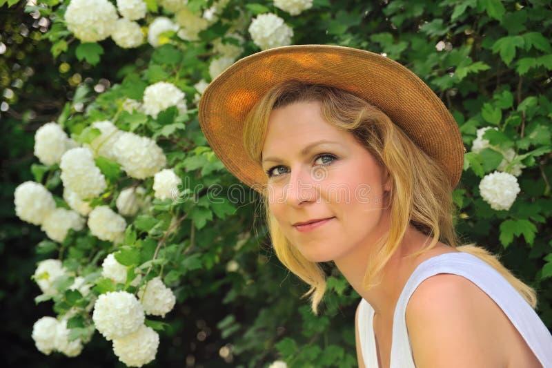 Jonge vrouw die in tuin rust royalty-vrije stock foto's