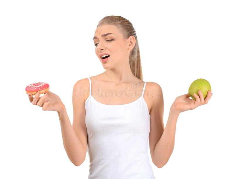 Jonge vrouw die tussen doughnut en appel op witte achtergrond kiezen Het concept van het dieetvoedsel stock afbeeldingen