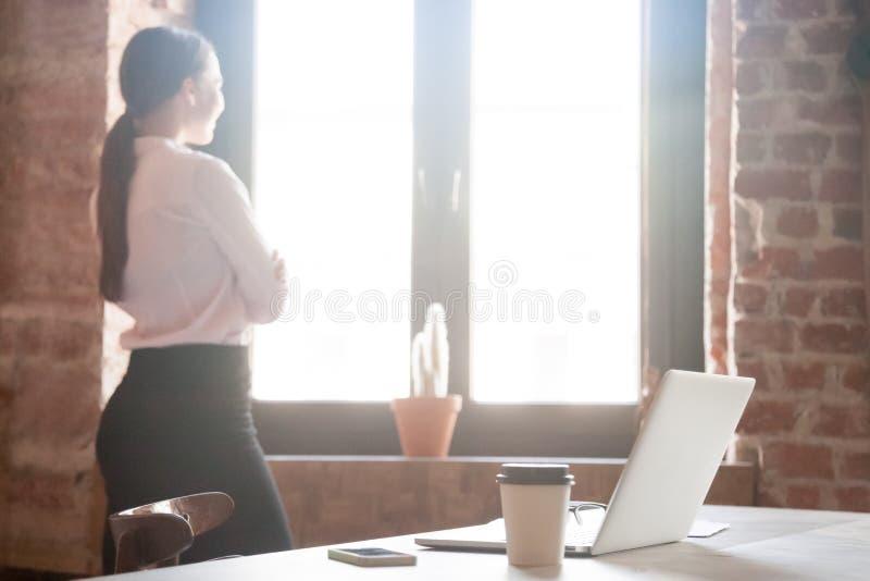 Jonge vrouw die uit venster in bureau kijken stock foto
