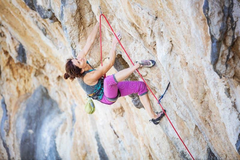 Jonge vrouw die uitdagingsroute op overhangende klip beklimmen stock fotografie