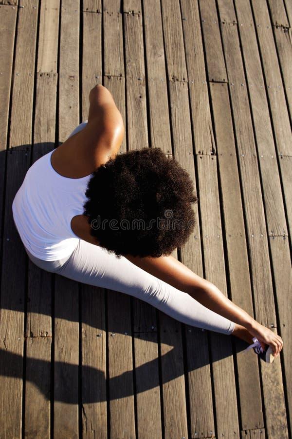 Jonge vrouw die uitrekkende oefening doen bij strand stock foto's