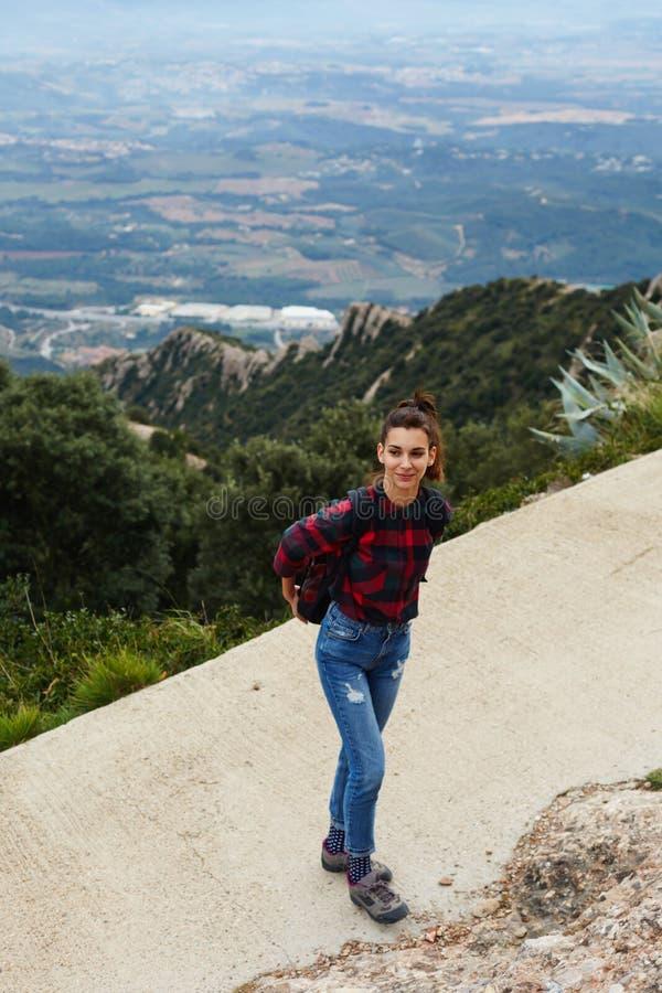 Jonge vrouw die van aard genieten terwijl uit wandeling in bergen royalty-vrije stock foto