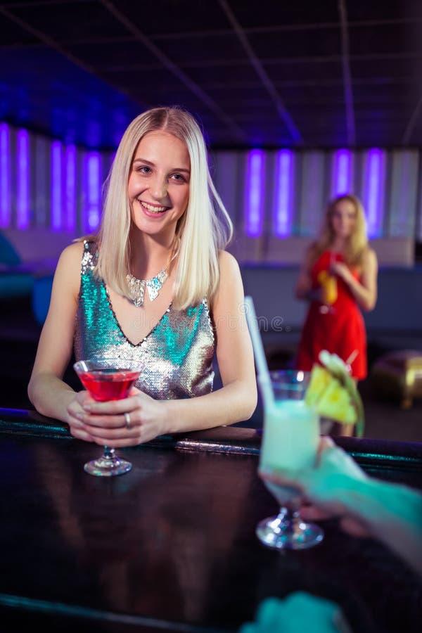 Jonge vrouw die van cocktail genieten bij barteller royalty-vrije stock fotografie