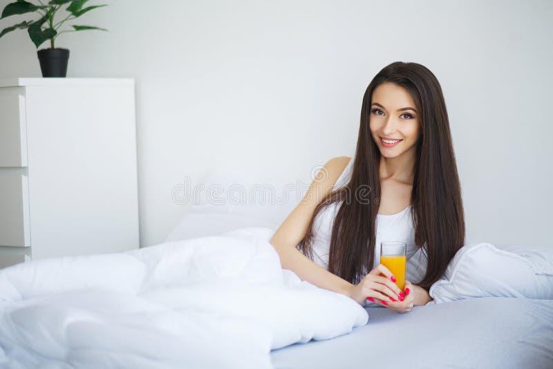 Jonge vrouw die van een glas jus d'orange in de ochtend genieten als s stock fotografie