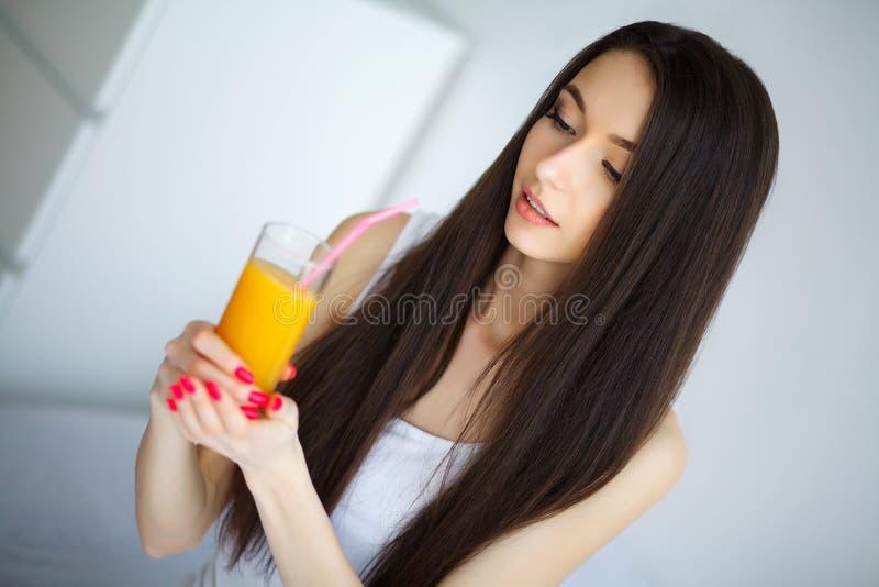 Jonge vrouw die van een glas jus d'orange in de ochtend genieten als s stock afbeeldingen