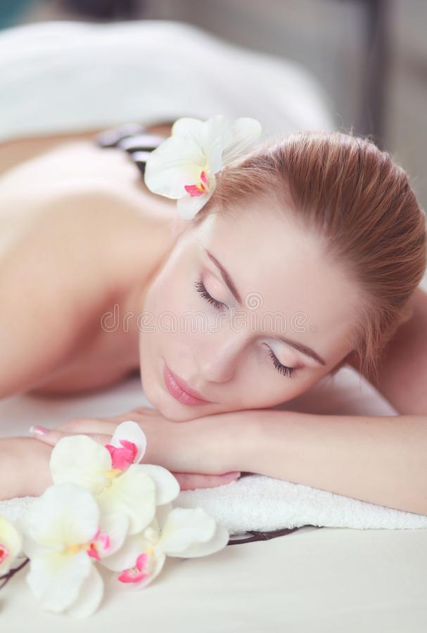 Jonge vrouw die van een hete rotsmassage in een kuuroordsalon en een witte bloem op haar hoofd genieten stock afbeeldingen