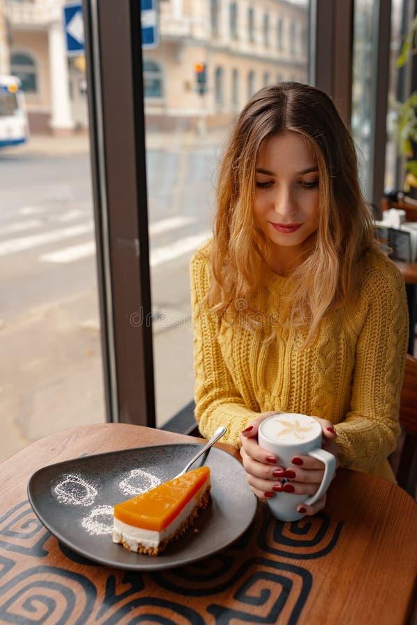Jonge vrouw die van een kop van koffie en van een plak van heerlijke ca genieten royalty-vrije stock fotografie