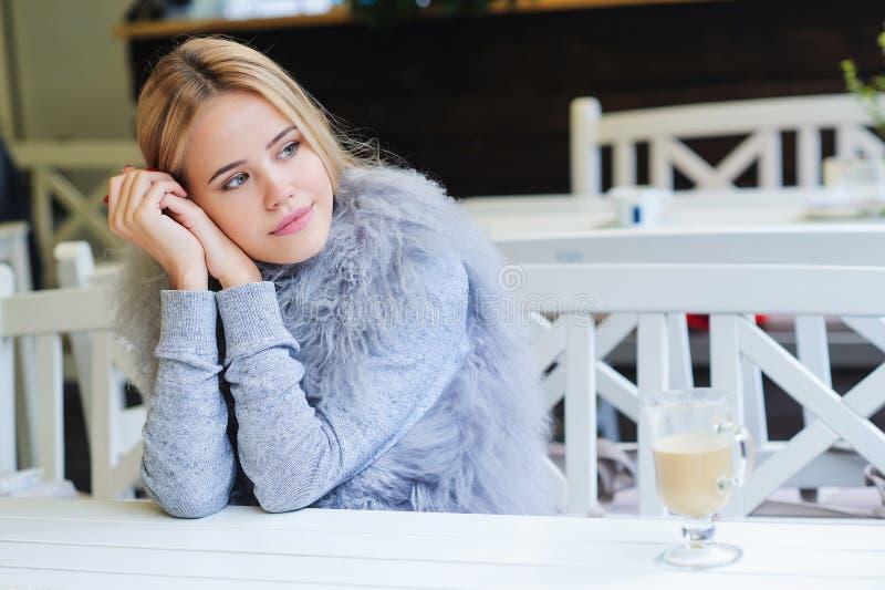 Jonge vrouw die van haar tijd genieten tijdens koffiepauze stock foto's