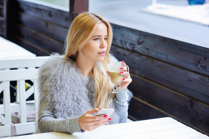 Jonge vrouw die van haar tijd genieten tijdens koffiepauze royalty-vrije stock foto
