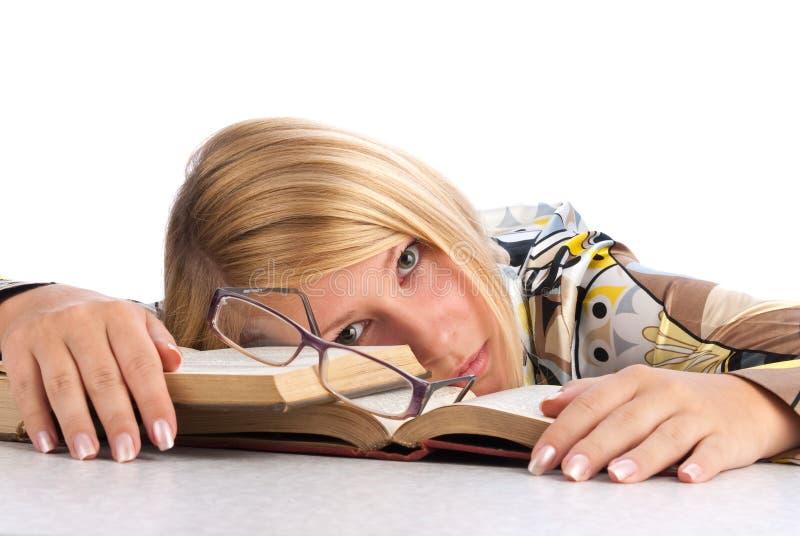 Jonge vrouw die van het bestuderen wordt vermoeid stock foto