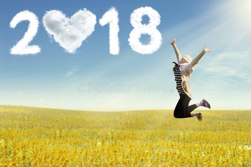 Jonge vrouw die van het nieuwe jaar genieten die op gebied springen royalty-vrije stock afbeelding