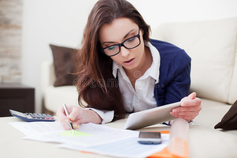 Jonge vrouw die van huis werken die digitale tablet gebruiken stock afbeelding