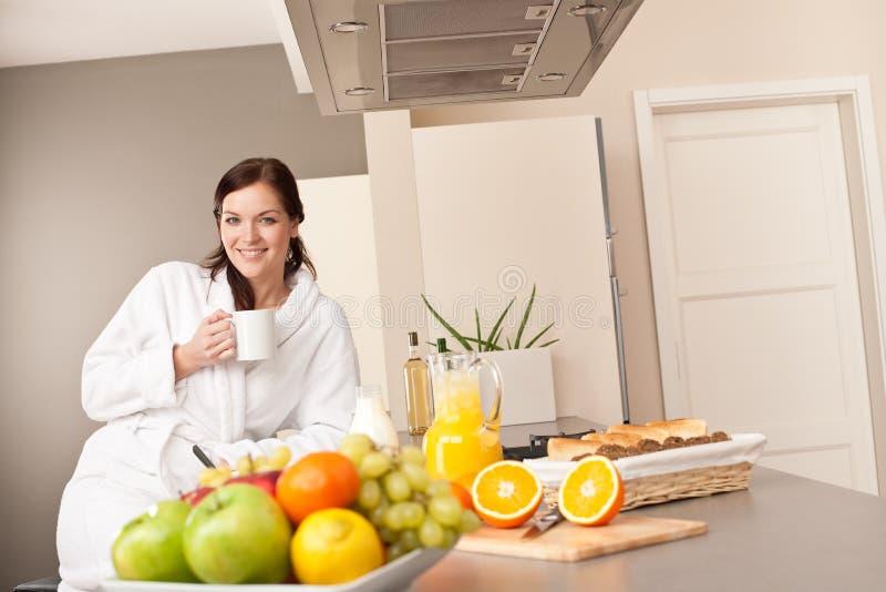 Jonge vrouw die van koffie in keuken geniet stock afbeelding
