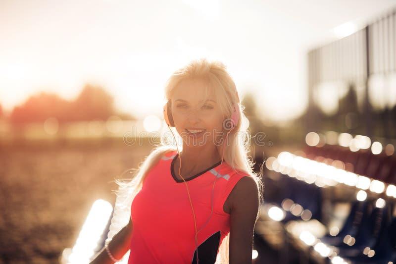 Jonge vrouw die van muziek op het strand genieten stock foto's