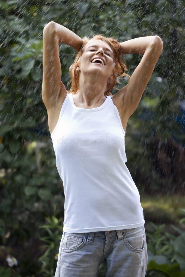 Jonge vrouw die van regen geniet stock foto's