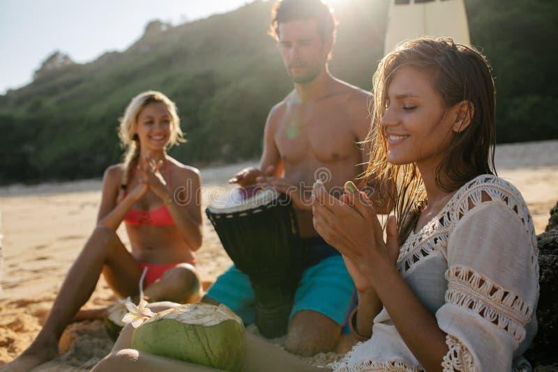 Jonge vrouw die van vakantie met haar vrienden op het strand genieten stock foto's