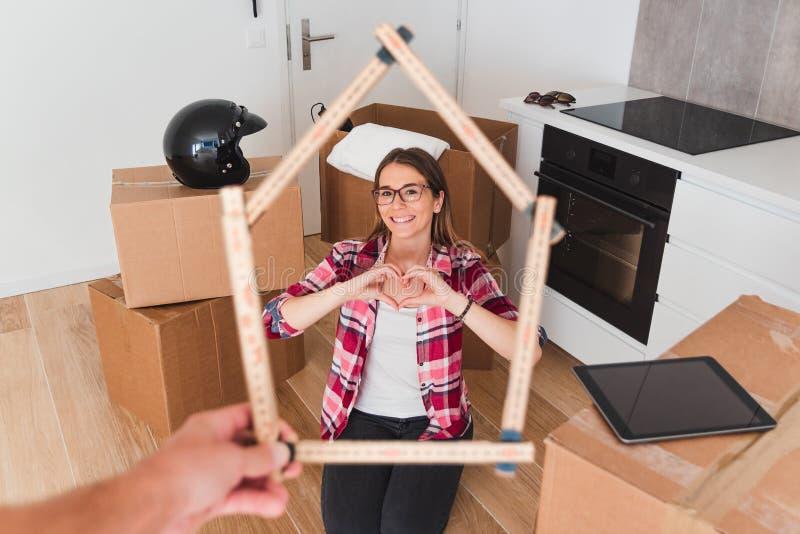 Jonge vrouw die van zijn nieuw huis, hartvorm genieten royalty-vrije stock foto