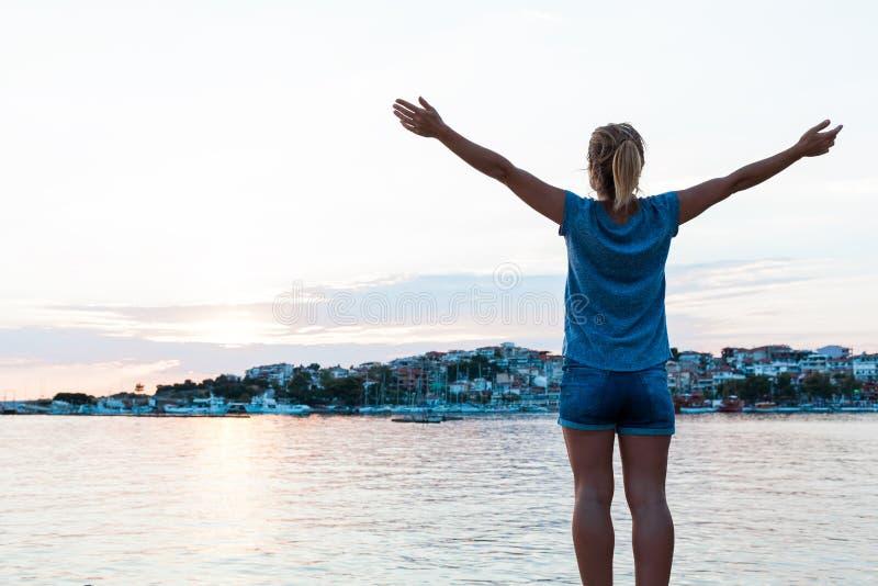 Jonge vrouw die van zonsondergang in de kust genieten stock afbeelding