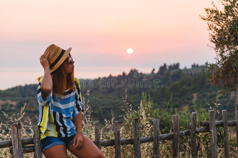Jonge vrouw die van zonsondergang genieten door de kust royalty-vrije stock afbeelding