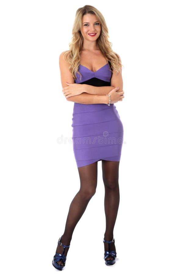 Jonge Vrouw die vast Dragend Purper Kort Mini Dress With Arms Folded en Hoge Hielen glimlachen stock foto