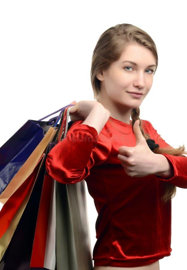 Jonge vrouw die vele het winkelen zakken, duimen omhoog dragen. royalty-vrije stock foto's