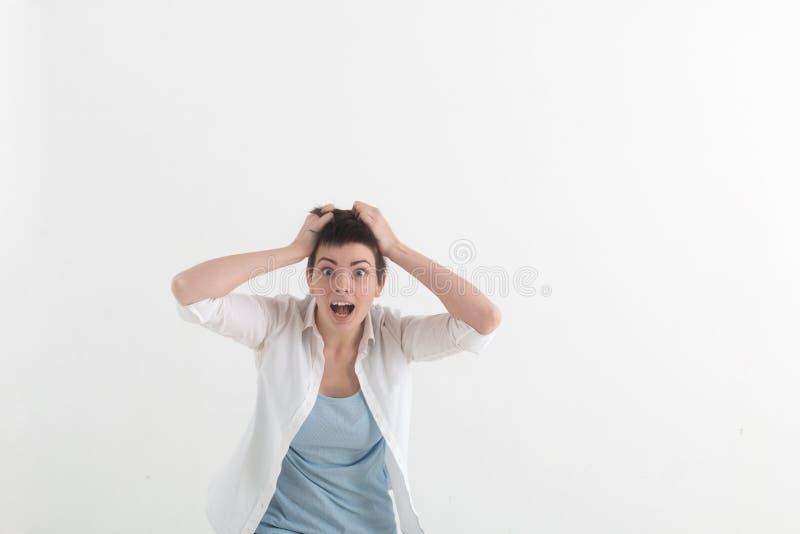 Jonge vrouw die in verschrikking met handen op haar hoofd, mond wijd het open bekijken in paniek gillen de camera Sluit omhoog royalty-vrije stock afbeelding