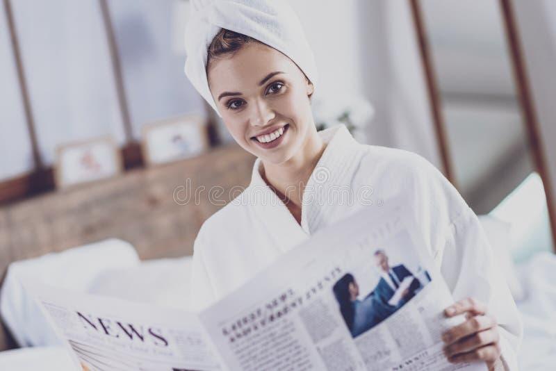 Jonge vrouw die verse krant houden stock afbeeldingen