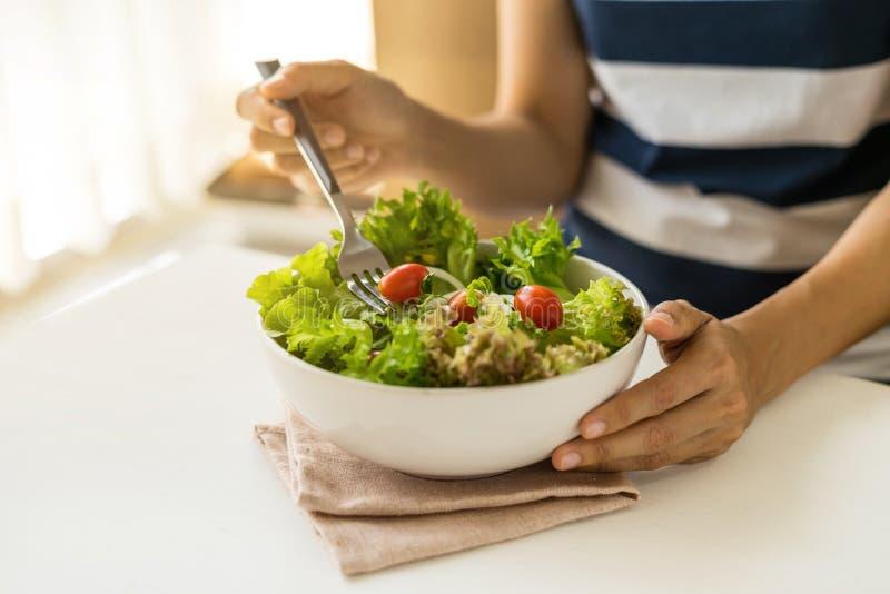 Jonge vrouw die verse organische vegetarische salade eten stock afbeeldingen
